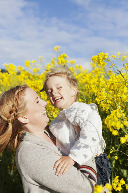 Woman carrying cheerful son — Stock Photo