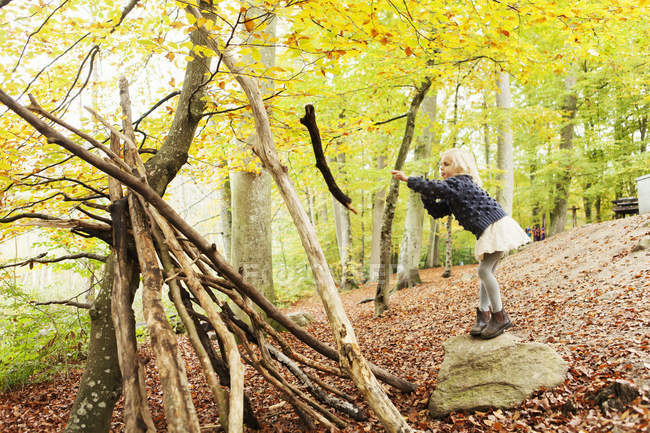 Girl throwing log in forest — Stock Photo