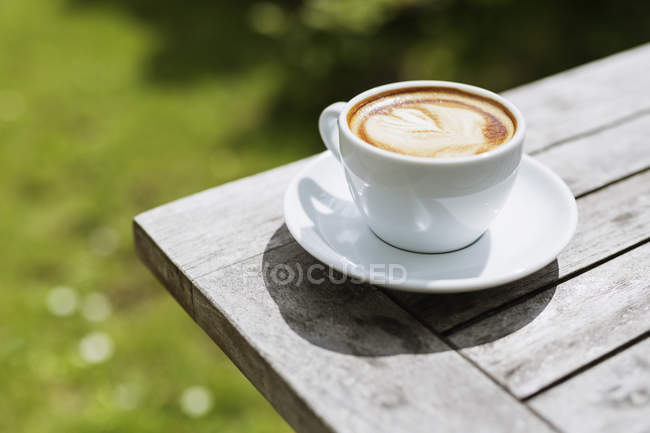 Cappuccino on wooden table — Stock Photo