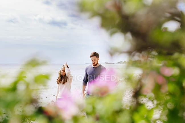 Giovane coppia a piedi in spiaggia — Foto stock