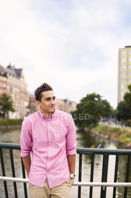 Улыбающийся человек, стоящий у ограды — стоковое фото