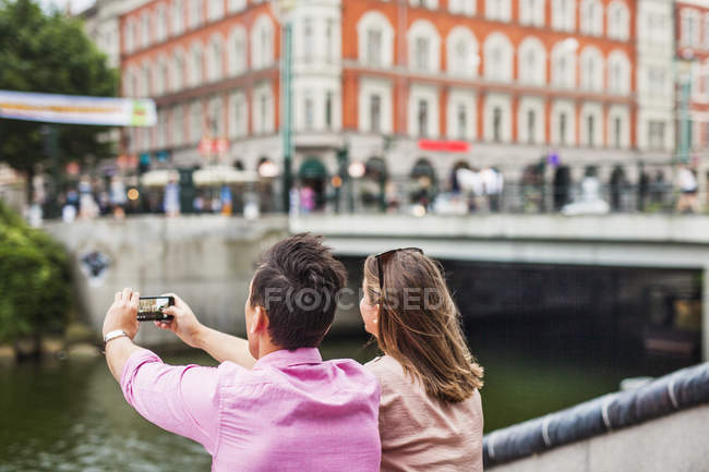 Man standing by friend photographing buildings — Stock Photo