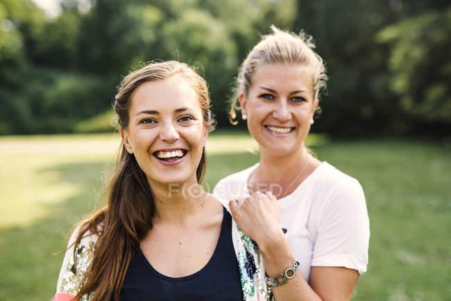 Lächelnde Freunde im Park — Stockfoto