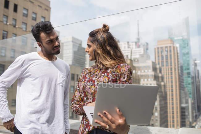 Femme montrant un ordinateur portable à un collègue — Photo de stock
