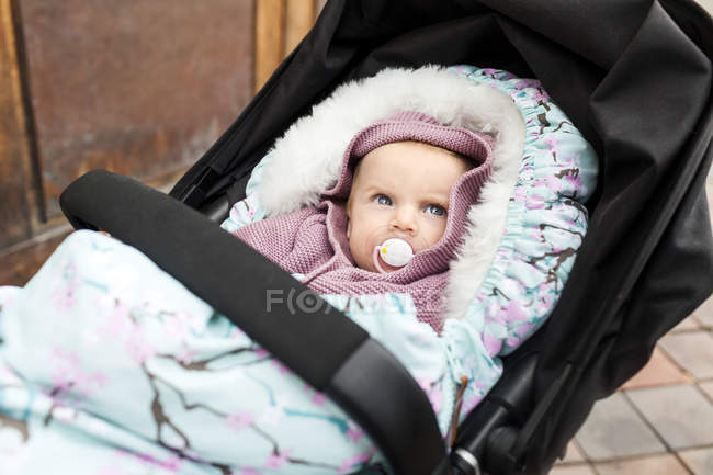 Baby girl with pacifier in carriage — Stock Photo
