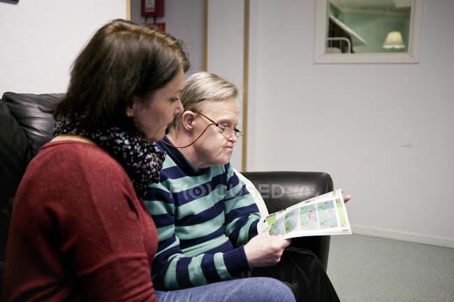 Caregiver looking at mentally challenged senior — Stock Photo