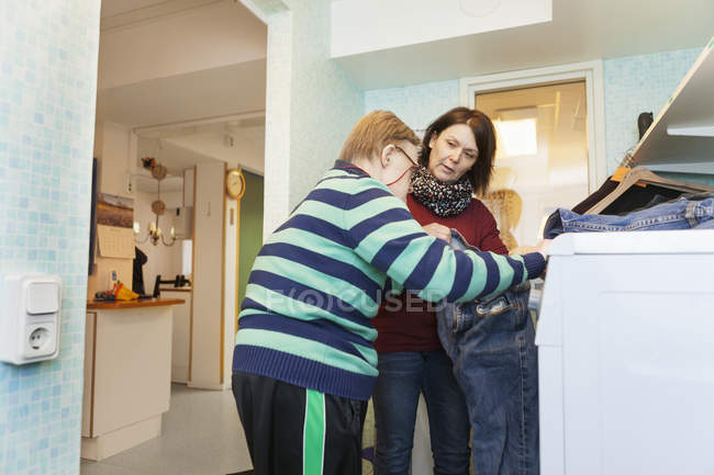 Senior man washing clothes with caregiver — Stock Photo