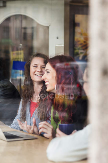 Happy friends sitting at cafe — Stock Photo