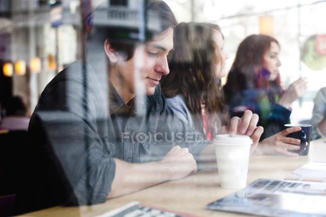 Людина з кави, сидячи друзів — стокове фото