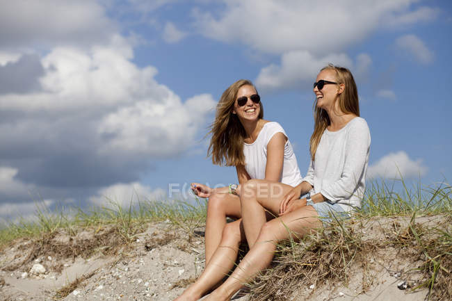 Cheerful friends sitting on sand — Stock Photo