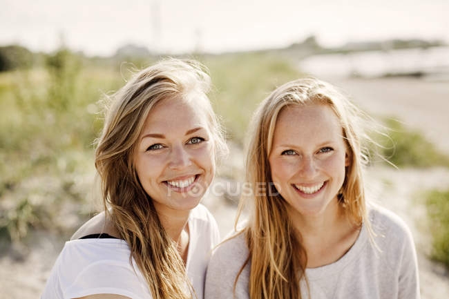 Happy female friends enjoying at beach — Stock Photo