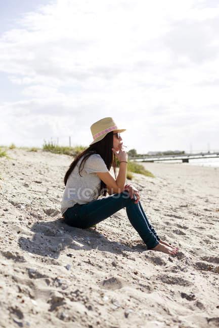 Young woman smoking at beach — Stock Photo