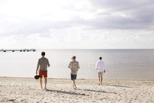 Чоловіки, друзі прогулянки по відношенню до моря — стокове фото