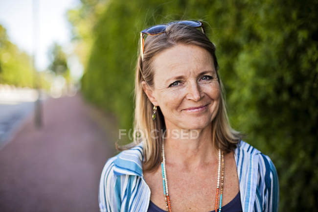 Mature woman smiling on sidewalk — Stock Photo