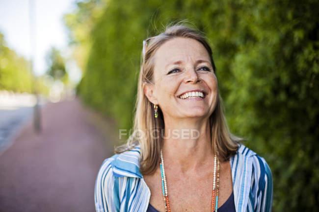 Зрелая женщина улыбается на тротуаре — стоковое фото