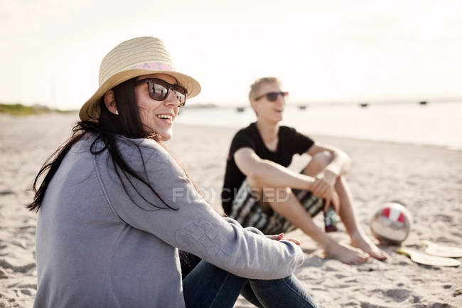 Young woman sitting with male friend — Stock Photo