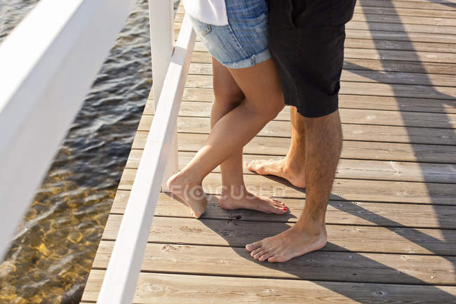 Couple standing by railing on pier — Stock Photo