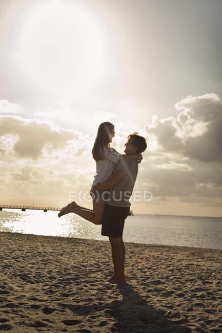 Man carrying woman at beach — Stock Photo