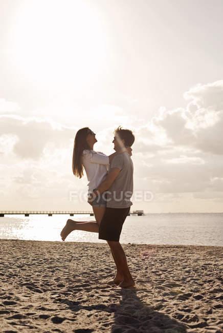 Man carrying girlfriend at beach — Stock Photo