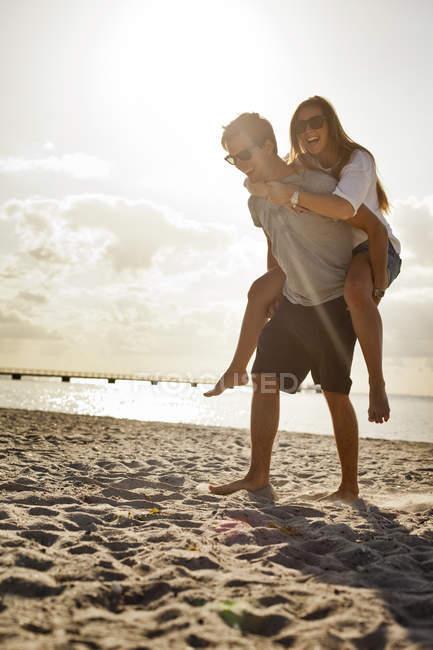 Couple profitant d'une balade à dos de cochon à la plage — Photo de stock