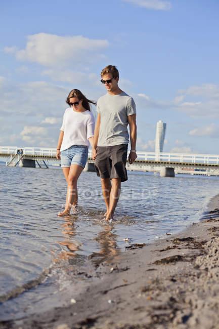 Couple tenant la main tout en marchant dans la mer — Photo de stock