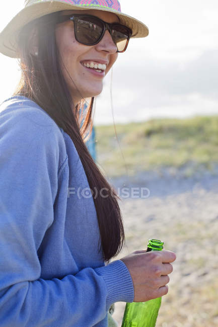 Woman holding beer bottle at beach — Stock Photo