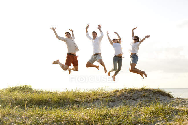 Young friends jumping at beach — Stock Photo