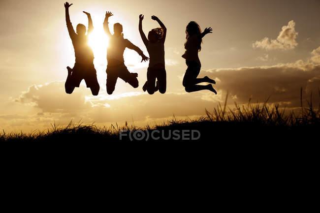 Молодые друзья, прыгающие на пляже — стоковое фото