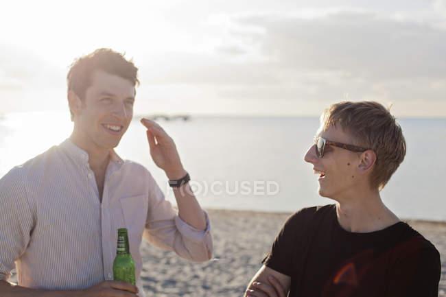 Amis masculins parlant à la plage — Photo de stock