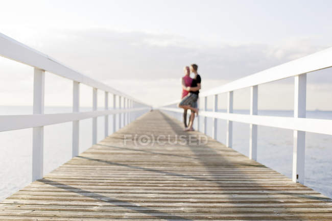 Young couple kissing on pier — Stock Photo