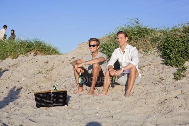 Amis souriants tenant des bouteilles de bière — Photo de stock