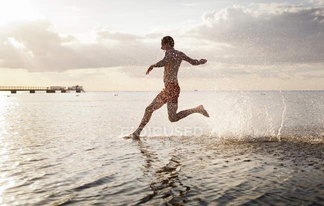 Молода людина, що біжить в море — стокове фото