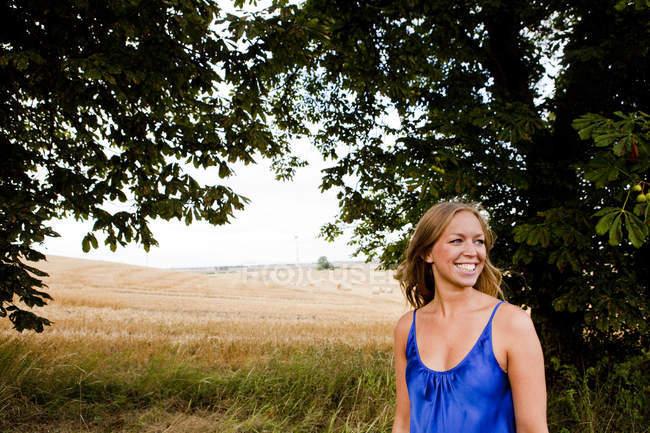 Жінка фотографіях хтось дивитися вбік, поки стоїть на полі — стокове фото