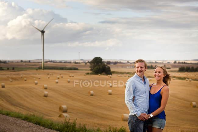 Пара, тримаючись за руки, поки стоїть на полі — стокове фото
