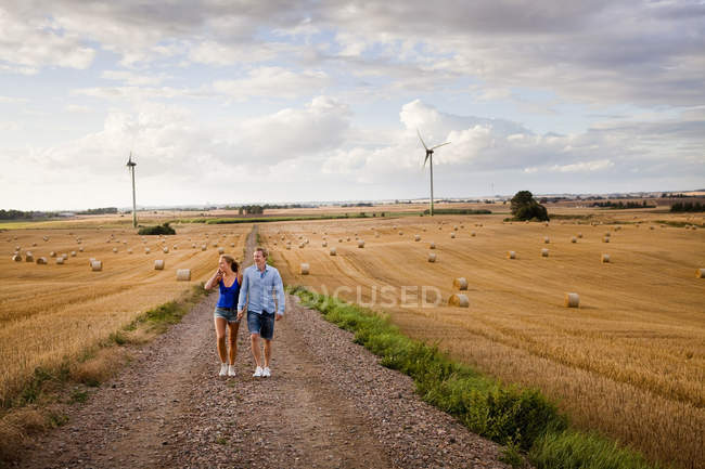Couple walking on dirt road by field — Stock Photo