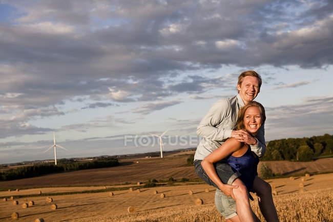 Жінка даючи людини piggyback їздити на полі — стокове фото
