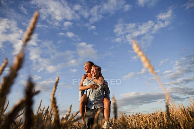 Людина, даючи piggyback жінка на полі — стокове фото
