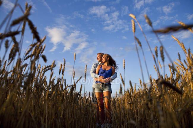 Пара стоячи на полі проти неба — стокове фото