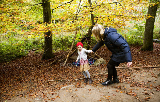 Playful mother and daughter in forest — Stock Photo