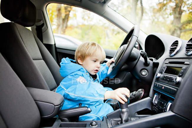 Cute boy sitting on drivers seat — Stock Photo