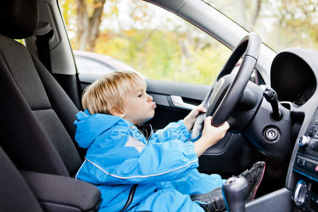 Boy puckering lips while driving car — Stock Photo