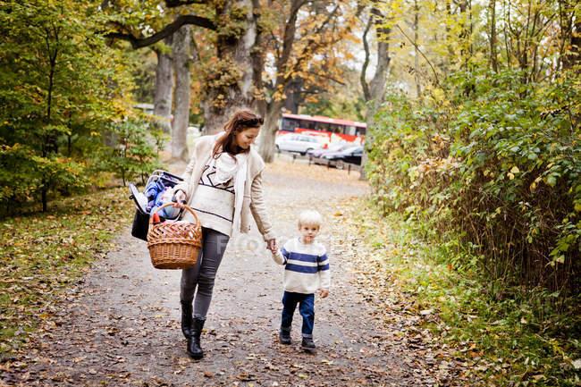 Frau mit Korb während des Gehens mit jungen — Stockfoto
