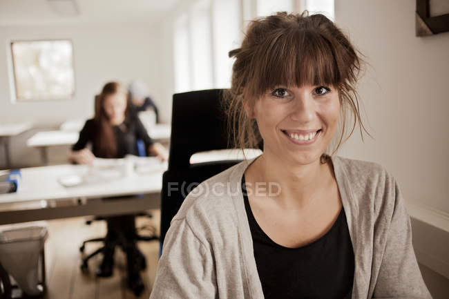 Businesswoman sitting in creative office — Stock Photo