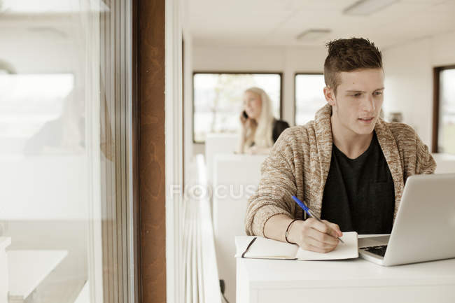 Man writing while using laptop — Stock Photo
