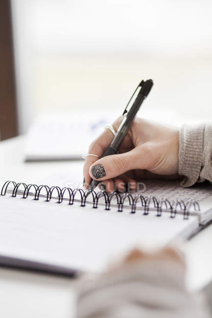 Hand writing in spiral notebook — Stock Photo