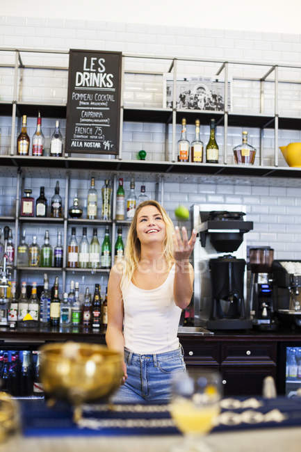 Happy woman juggling at counter — Stock Photo