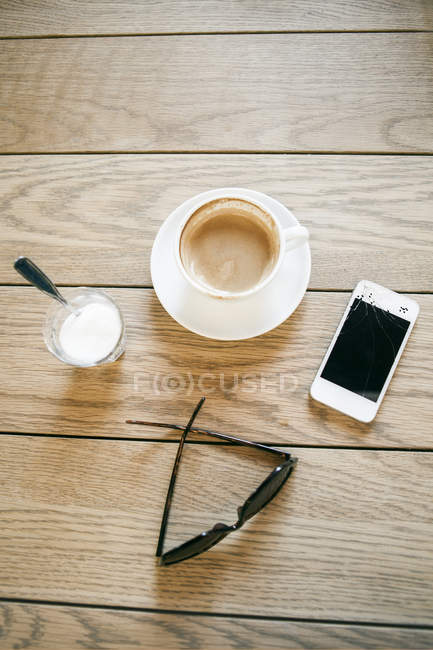 Coffee cup with broken smart phone — Stock Photo
