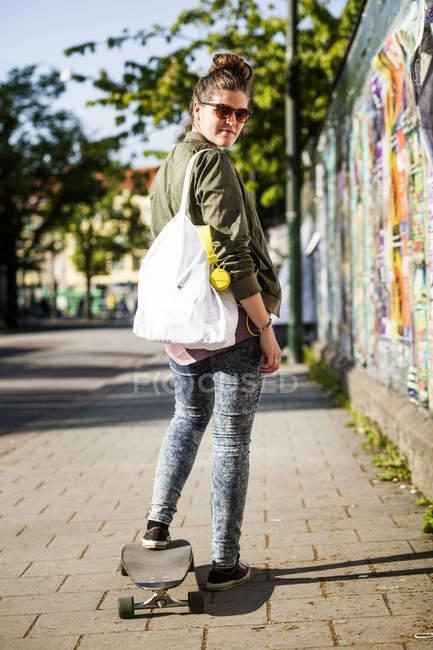 Woman standing on skateboard — Stock Photo
