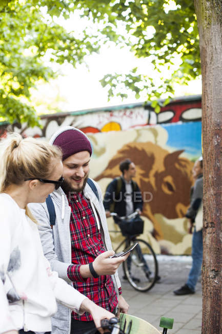 Friends using smart phone — Stock Photo