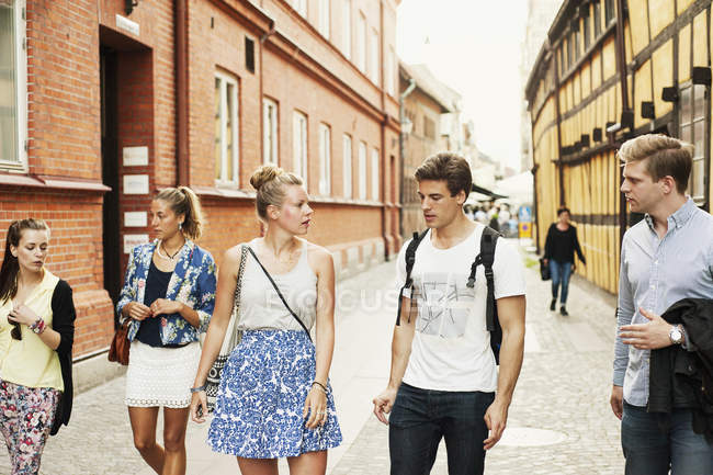 Friends talking while walking on city — Stock Photo